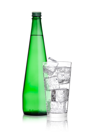 Bottle and glass with healthy sparkling  water lemonade with ice cubes on white