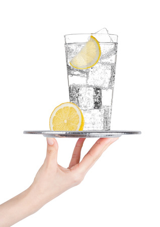 Hand holds tray with sparkling water soda drink with ice and lime lemon slice on white background Stock Photo