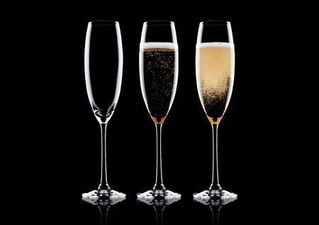 Elegant glasses of yellow champagne with bubbles on black background with reflection Standard-Bild