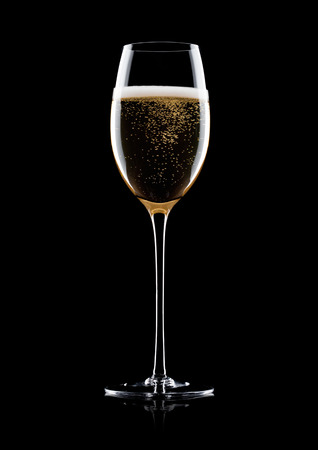 Elegant glass of yellow champagne with bubbles on black background with reflection Foto de archivo