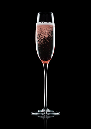 Rose pink champagne glass with bubbles on black background with reflection Standard-Bild
