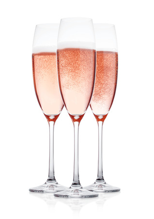 Elegant Rose pink champagne glasses with bubbles  on white background with reflection