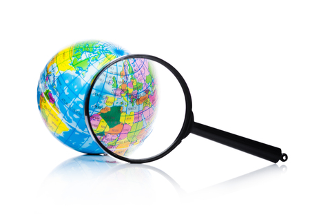 Globe under magnifying glass zooming Europe and Africa on white background Stock Photo