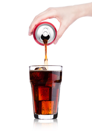 Female hand pouring cola soda drink from aluminium can to glass  with ice cubes on white background