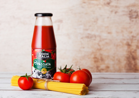 LONDON, UK - MARCH 10, 2018 : Glass bottle of Cook Italia Passata Sauce with spaghetti and raw tomatoes on wooden background.