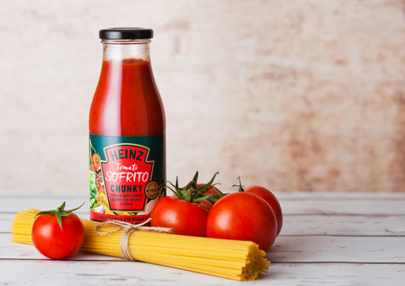 LONDON, UK - MARCH 10, 2018 : Glass bottle of Heinz tomato sofrito Chunky tomato base on wooden background with spaghetti.