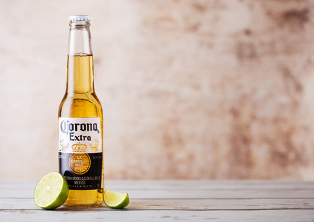 LONDON, UK - MARCH 10, 2018 : Bottles of Corona Extra Beer with lime slice on wooden background.Corona is the most popular imported beer in the US. Editöryel