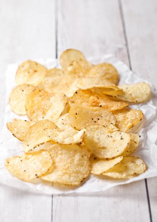 Crispy delicious pepper potato crisps chips snack on white wooden and paper Stock Photo