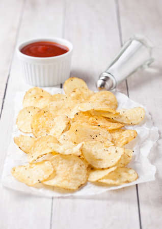Crispy delicious pepper potato crisps chips snack on white wooden board with sauce and salt Stock Photo