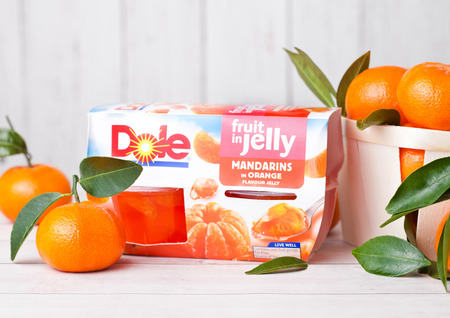 LONDON, UK - MARCH 31, 2018: Pack of Dole Mandarin Segments Jelly with fresh fruits on white wooden background. Stock Photo - 105183392