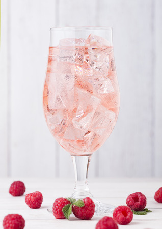 Glass of cold raspberry cider with ice cubes and fresh berries on light wooden background 写真素材