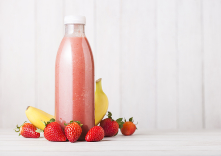 Plastic bottle with fresh summer berries smoothie on wooden background.Strwberry and banana flavour. 스톡 콘텐츠