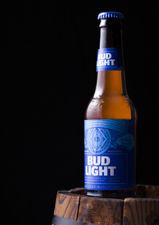 LONDON, UK - MAY 03, 2018: Glass bottle of Budweiser Bud Light Beer on dark wooden barrel An American lager first introduced in 1876.