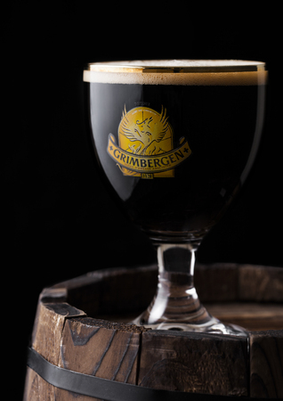 LONDON, UK - MAY 03, 2018: Cold Glass of Grimbergen dubbel beer on wooden barrel and black background.