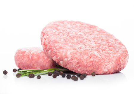 Raw fresh beef burgers with pepper and rosemarine on white background Stock Photo