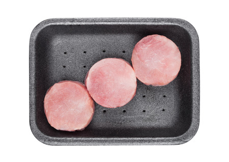 Raw round pork steak slices in plastic tray container on white
