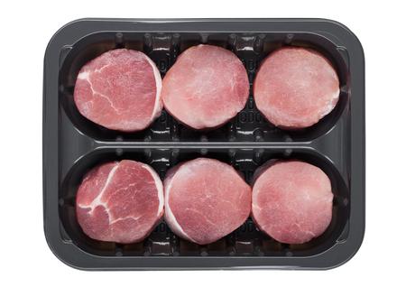 Raw round pork steak slices in plastic tray container on white