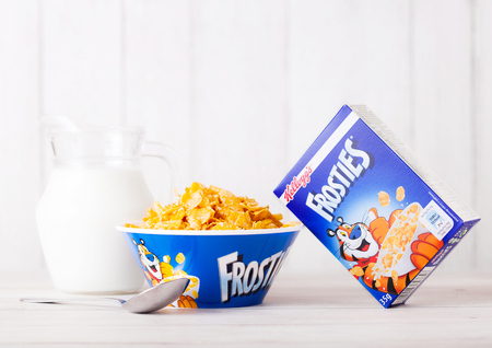 LONDON, UK - JUNE 01, 2018: Box of Kelloggs Frosties Breakfast Cereal with milk and plate on white wooden background.
