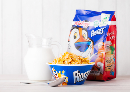 LONDON, UK - JUNE 01, 2018: Pack of Kelloggs Frosties Breakfast Cereal with milk and plate on white wooden background.