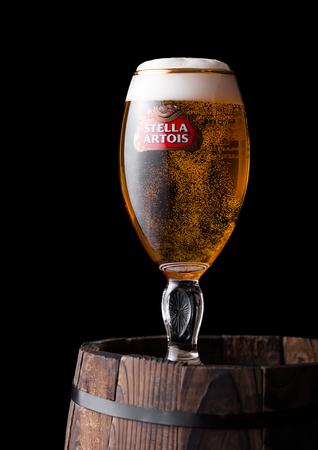 LONDON, UK - JUNE 06, 2018: Cold glass of Stella Artois beer on old wooden barrel  on black background. Editorial