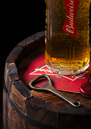 LONDON, UK - APRIL 27, 2018: Original glass of budweiser beer with beer coater and bottle opener on wooden barrel., an American lager first introduced in 1876. Editorial