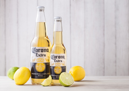LONDON, UK - APRIL 27, 2018: Bottles of Corona Extra Beer on wooden background with fresh lemons and limes . Corona, produced by Grupo Modelo.
