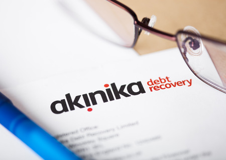 LONDON, UK - AUGUST 18, 2018: Akinika leading UK debt collection agency statement with glasses and pen. Editorial