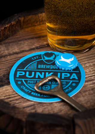 LONDON, UK - AUGUST 10, 2018: Brewdog Punk Ipa beer coaster with bottle top and opener and glass of beer on top of wood barrel.