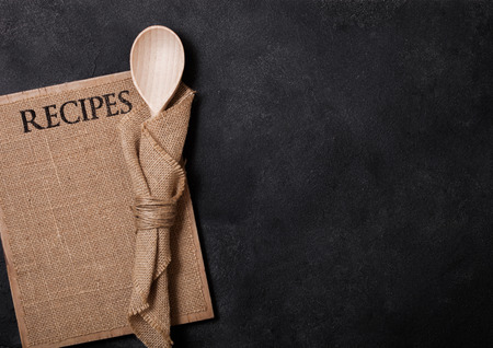 Vintage kitchen wooden utensils with linen recipes board on stone table background. Top view.