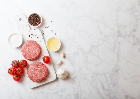 Raw minced homemade grill beef burgers with spices and herbs. Top view and space for text. On top of chopping board and marble  kitchen table background. With pepper salt and oil. 免版税图像