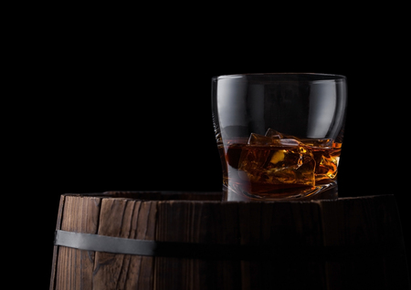 Glass of whiskey with ice cubes on top of wooden barrel. Cognac and brandy drink Reklamní fotografie
