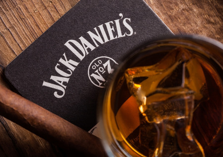 LONDON, UK - SEPTEMBER 04, 2018: Glass of Jack Daniels whiskey with original coaster and cigar on wooden board.