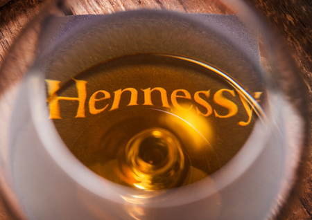 LONDON, UK - SEPTEMBER 04, 2018: Glass of Hennessy Cognac with original coaster on top of wood. Zdjęcie Seryjne - 111248975