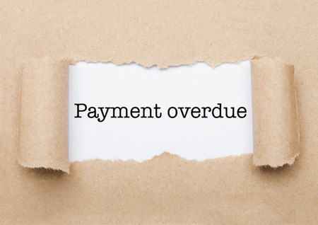 Payment Overdue concept text appearing behind torn brown paper envelope