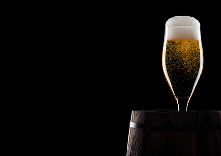 Cold glass of craft beer on old wooden barrel on black background with dew and bubbles. With space for your text.