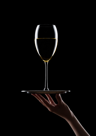 Hand holds tray with glass of white wine on black background