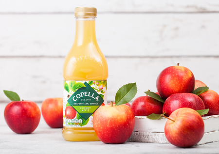 LONDON, UK - SEPTEMBER 13, 2018: Plastic bottle of fresh Copella Apple Juice with fresh apples in box on wood background. Editorial