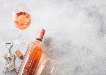 Bottle and glasses of pink rose wine with cork and corkscrew opener on stone kitchen table background. Top view. Banque d'images