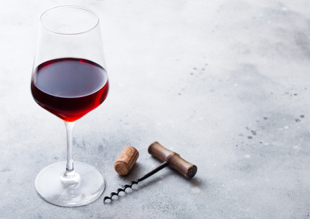 Elegant glass of red wine with cork and opener on kitchen table background.