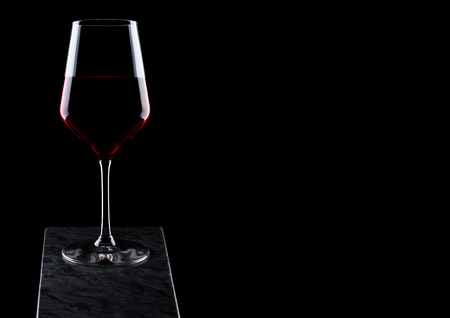 Glass of red wine on wooden board on black background. Archivio Fotografico