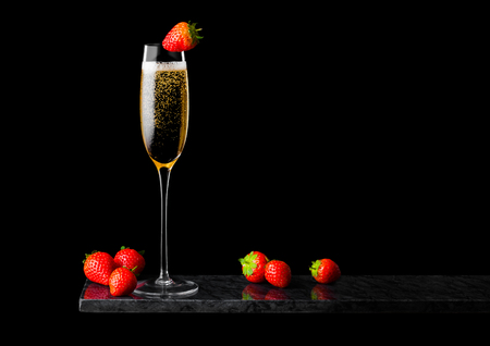 Elegant glass of yellow champagne with strawberry on top and fresh berries on black marble board on black.