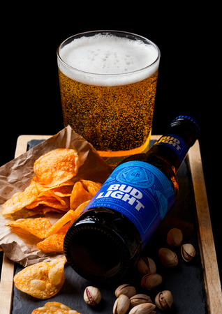 LONDON, UK - SEPTEMBER 26, 2018: Bottle of Bud Light beer with glass and snack ostone board on black. Pistachios and pretzel and chips Editoriali