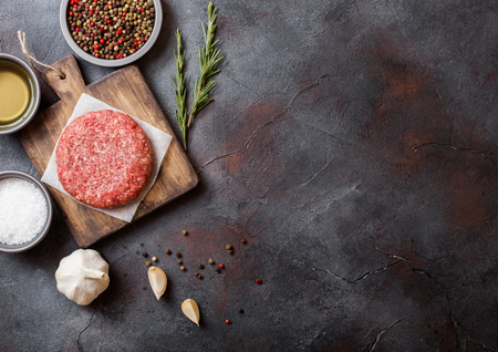 Raw minced homemade grill beef burgers with spices and herbs. Top view and space for text. On top of chopping board and kitchen table background. With pepper salt and oil.