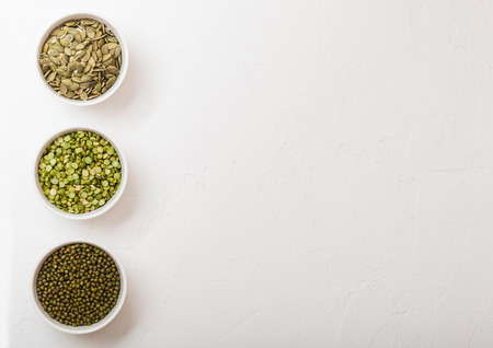 Bowl of mung beans and split peas and pumkin seeds on white kitchen background