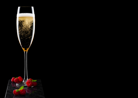 Elegant glass of yellow champagne with raspberries with mint leaf on black marble board on black background. Banco de Imagens