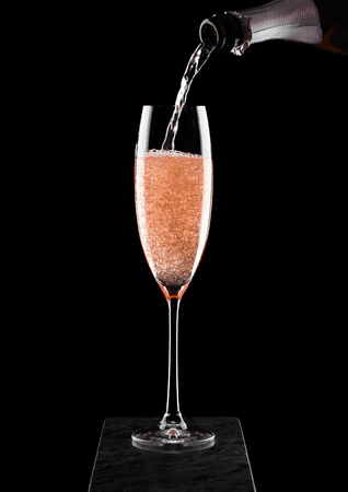 Pouring pink rose champagne from bottle to glass on black marble board on black background.