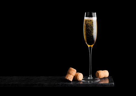 Elegant glass of yellow champagne with corks on black marble board on black.