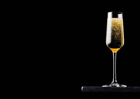 Elegant glass of yellow champagne with bubbles on black marble board on black background. Banco de Imagens