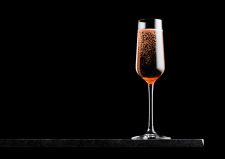 Elegant glass of pink rose champagne with bubbles on black marble board on black.