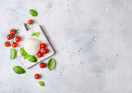 Fresh Mozzarella cheese on vintage chopping board with tomatoes and basil leaf on stone kitchen background.